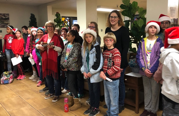 Chamisa K-Kids spread holiday cheer to the residents at Sombrillo. Sixth grade teacher, Cindy Richard, joined in the singing accompanied by ukulele & piano with Kim Letellier, music teacher